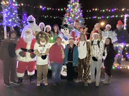 Volunteers dressed up as holiday characters in front of the trailer enjoy a fun night of caroling. (Photo by Martha Russell)