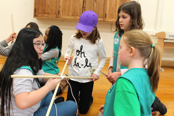Junior Girl Scouts work together to create a structure that will keep them dry in a flood.