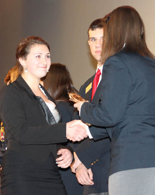Lewiston-Porter High School student Hannah Cupples accepts a trophy for her performance at the Region 12 DECA competition. Cupples was among hundreds of students competing in business-related events, and she was awarded for her effort in the public speaking (prepared) event. (photo by Larry Austin)