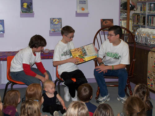 Nathaniel Swanson (center) along with Joshua Snow (left) and Kevin Bovanizer (right) read to children at the Youngstown Story Hour in October.