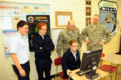 The 107th Airlift Wing has been mentoring Junior Reserve Officer Training Corps members at the Lewiston-Porter High School. The mission is called CyberPatriot. In the photo Brian Boyd, Matt O'Conner, Master Sgt. Joel Micoli and Chief Master Sgt. Mark Grier observed Ashlee Roell performing her cybersecurity task on Oct. 16. (U.S. Air Force photo by Senior Master Sgt. Ray Lloyd)