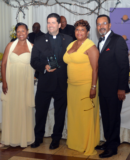 The Rev. James J. Maher, C.M., Niagara University president, is presented with the Trey Whitfield Foundation's 2015 Adult Honoree Award by event emcee Clifton Davis and members of the organization's board of trustees.