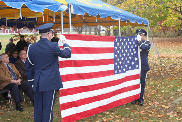 Members of Niagara Falls Air Base Honor Guard complete the American flag folding ceremony while explanations of its symbolism are explained to onlookers.