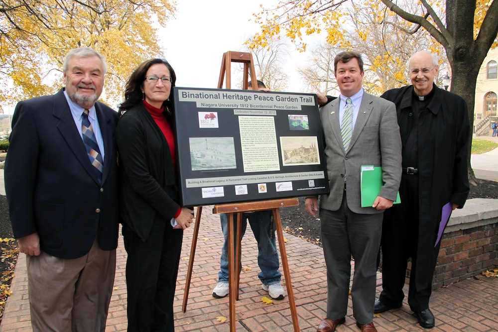 Brian Merrett, CEO of the 1812 Bicentennial Legacy Council; Arlene White, executive director of the Binational Tourism Alliance; Dr. Thomas Chambers, chair of Niagara University's history department; and the Rev. Joseph L. Levesque, C.M., NU president, spoke during Monday's unveiling of a commemorative plaque for the Niagara University 1812 Bicentennial Peace Garden. (photos by Brian Rock/Niagara University)