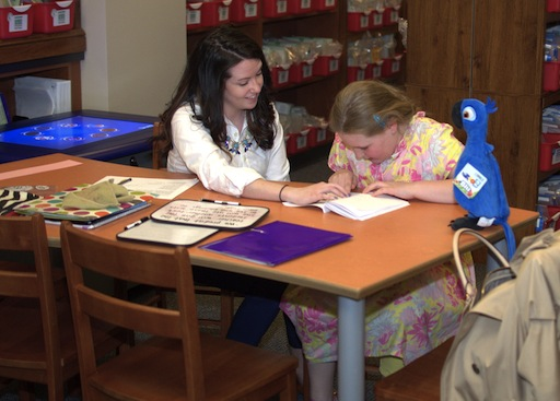 NU graduate student Kristen DeMarco works with a young student inside the Family Literacy Center.