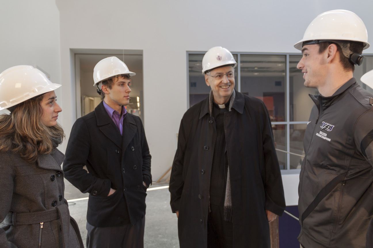 The Rev. Joseph Levesque, C.M., president of Niagara University, speaks with students inside the new B. Thomas Golisano Center for Integrated Sciences. The academic building is set to open this fall. (contributed photo)