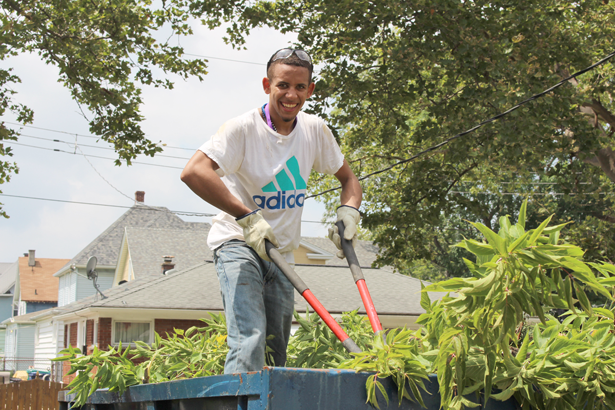 Incoming Niagara University freshman Hamlet Margarin smiles while trimming tree branches at a Niagara Falls home that's being rehabilitated by the Niagara Area Habitat for Humanity.