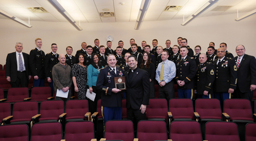 Framed by university administrators and ROTC cadets, Lt. Col. Paul Dansereau and the Rev. James J. Maher, C.M., proudly display the MacArthur Award.