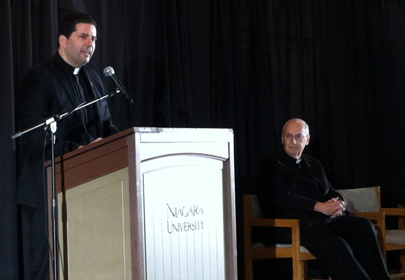 The Rev. James Mahar speaks to NU faculty and staff Wednesday as the Rev. Joseph Levesque, president, listens in.
