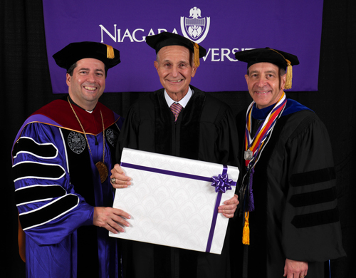 Jeremy M. Jacobs, chairman and CEO of Delaware North Companies and owner of the NHL's Boston Bruins, receives a framed honorary doctorate from the Rev. James J. Maher, C.M., president of Niagara University, and Dr. Gary Praetzel, dean of NU's College of Hospitality and Tourism Management.