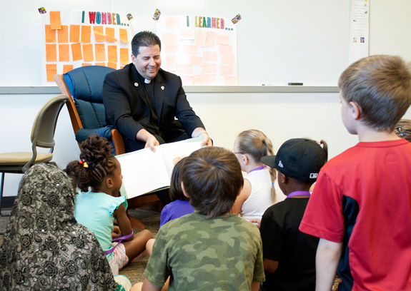 The Rev. James J. Maher, C.M., president of Niagara University, read `You're Here for a Reason` to the pre-K-2 students who attended NU's literacy camp this summer.