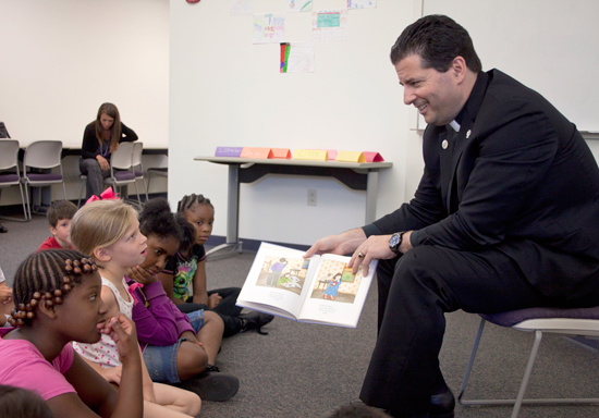 The Rev. James J. Maher, C.M., reads children a story as part of Niagara University's Primary Enhancement Program.