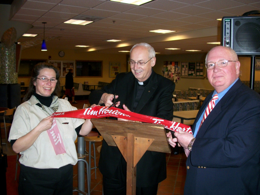Pictured, from left: Kim Rothschild, retail manager of hospitality services at Niagara University; the Rev. Joseph L. Levesque, NU president; and Bill Baker, general manager of hospitality services, cut the commemorative ribbon to celebrate the grand opening of a Tim Hortons Café & Bake Shop on the Niagara University campus.