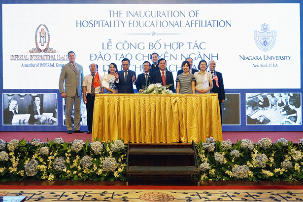 The Rev. James J. Maher, C.M., Niagara University president, center, is joined by Dr. Kurt Stahura, dean of NU's College of Hospitality and Tourism Management, far left, and Dr. Hung Le, vice president for international relations, far right, at an event to celebrate the establishment of the Imperial International Hotel School in Vung Tau, Vietnam.