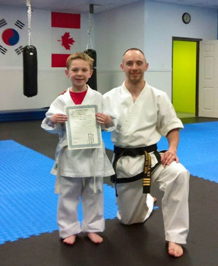 Owen Neri of North Tonawanda, who tested for his yellow stripe belt Tuesday night, is shown with David Prenatt of Nitro Martial Arts Academy in Wheatfield. Neri was the academy's first student. (Contributed photo.)