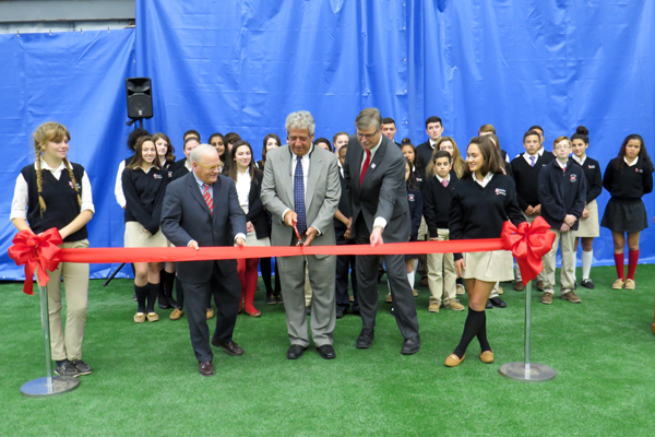 Niagara Catholic Jr./Sr. High School students look on as, from left, Principal/President Robert Cluckey, The Niagara Community Center's Gary Hall, and Niagara Falls Mayor Paul Dyster cut the ribbon on the new athletic and educational center.