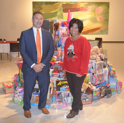 Pictured with the results of the Niagara Law Center's holiday toy drive are Paul Issac Sr., managing partner of Paramount Settlement Planning LLC, which sponsored the event, and Carol Howaart-Diez, CEO of the United Way of Greater Niagara.