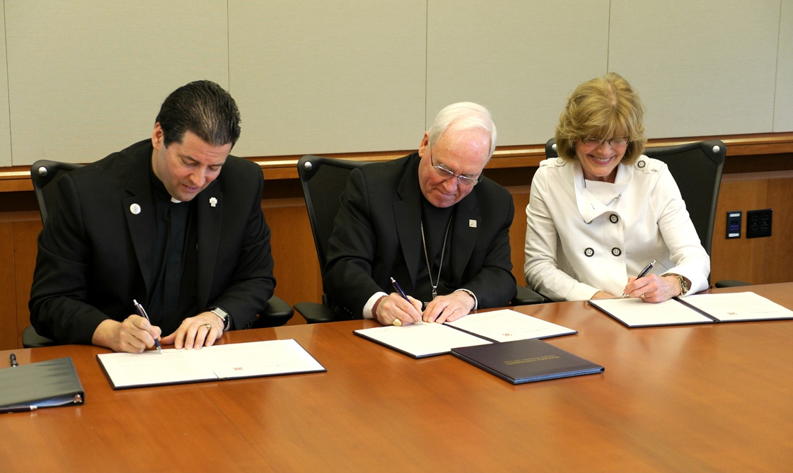 The Rev. James J. Maher, C.M., Bishop Richard Malone and Judith Nolan-Powell sign a memorandum of understanding (MOU) Friday morning.