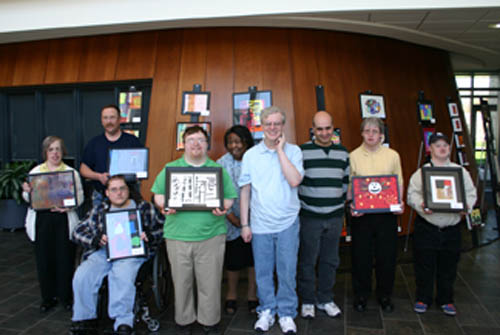 Pictured, from left: Artisans Unlimited participants Beverly Raff, Geoff Holly, Kerry Warner, Tim Conlin, Karen Armstrong, Stephen Dorgan, Peter Agugliaro, Alan Montaneri and Donald Smith pose with their artwork in Niagara University's Bisgrove Hall.