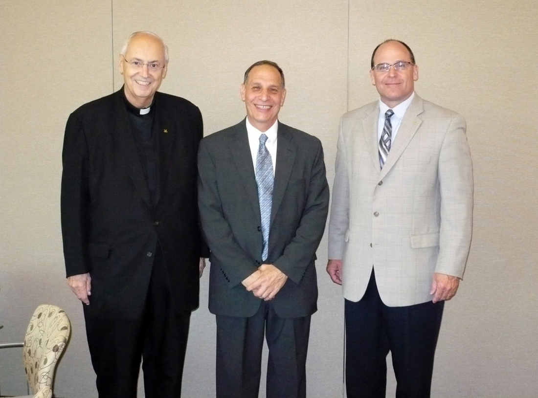 Al Oddo, center, was formally introduced as a professor emeritus during a reception held Nov. 15. The Rev. Joseph L. Levesque, NU president, and Timothy Downs, vice president for academic affairs, congratulated Oddo on his recognition.