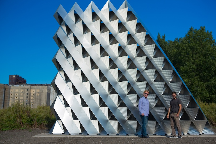 Christopher Romano (left) and Nicholas Bruscia stand in front of Project 2XmT, a sculptural wall they built at the gateway to Silo City in Buffalo. (photo by Douglas Levere, University at Buffalo)