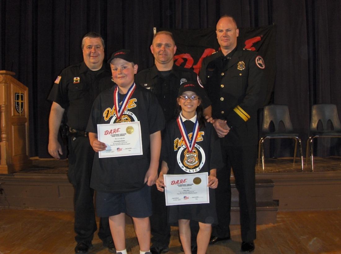 D.A.R.E. essay contest winners Christopher Belter and Ellen Diez display their award certificates with Lewiston Police officers John Penzotti and Scott Stafford and LPD Chief Chris Salada.