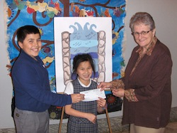 SNEP students Michael Trapasso and Natalie Diez present Stella Niagara Principal Sister Margaret Sullivan with a check for $300 to be donated to Heifer International.