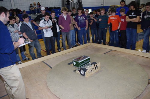 Lewiston-Porter's Brandon Davis mans the controls of SeaBiscuit Sr., a sumo robot he built with teammate Sam Buccella, standing to Davis' left. Davis and Buccella won this semifinal match to advance to the finals, where they placed second. (photo by Larry Austin)