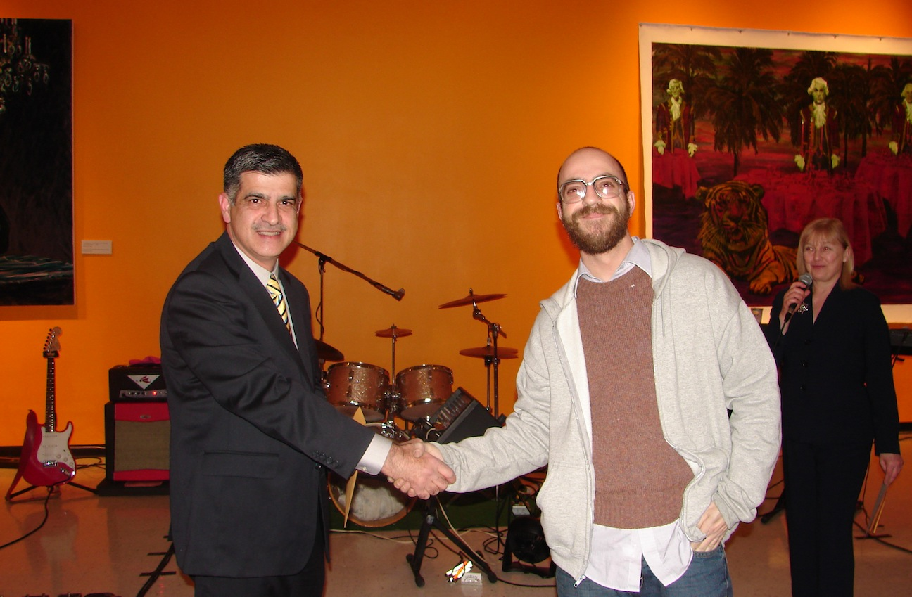 Sam Qureshi, manager of Tops Markets on Niagara Falls Boulevard, congratulates Buffalo artist Tom Holt, first-place winner of the `TopSpin 10` Community Choice Award. The presentation took place at the Castellani Art Museum's annual holiday bash on Dec. 14.