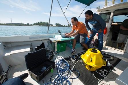 Zahed Hossain and Hovannes Kulhandjian, doctoral candidates in Tommaso Melodia's lab, (above), dropped two, 40-pound sensors into the water and then typed a command into a laptop. (photo by Douglas Levere)