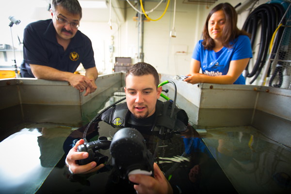 David Hostler, left, chair of exercise and nutrition sciences at UB, begins research on a UB study examining the dangers dehydration presents for U.S. Navy divers. Working with Hostler are diver Connor Meyer, a biology and exercise science major at Virginia Military Institute, and UB physical therapy major Laura Barnes. (Photo by Douglas Levere).