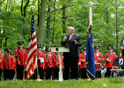 Niagara County Clerk Wayne F. Jagow delivers Memorial Day remarks at the Mount View Cemetery in Pekin standing in from on a memorial dating to the end of the Civil War and surrounded by members of the Sanborn Fire Company's band. Jagow urged an audience of approximately 100 people to take time to thank those who served, and discussed the County Clerk's Office's unique `Thank a Vet` program.