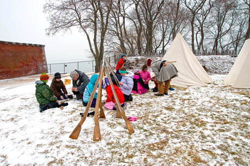 The young participants who portrayed a French military unit on a winter journey make camp and learn to make a fire with flint and steel so that they may pool their rations and cook pea soup. (photo by Wayne Peters)