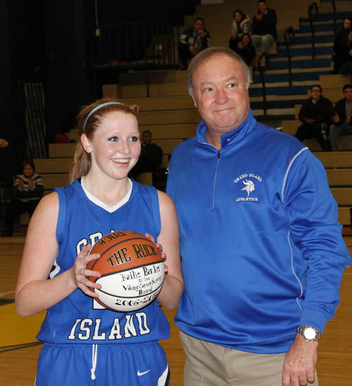 Kallie Banker received a game ball from Grand Island High School Athletic Director Jon Roth moments after breaking the school's basketball scoring record in a 42-16 win at Niagara Falls last Thursday. Carlin Hartman scored 1,518 points in his Vikings career. Banker needed eight points to break the record and ended up with 15 in the victory. (photo by Larry Austin)