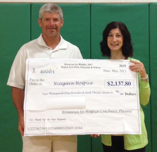 Lewiston-Porter varsity baseball coach Mark Waple presents a check for $2,137.80 to Maureen Rizzo of Niagara Hospice. Waple is the organizer of the `Homerun for Hospice` tournament, which included varsity and junior varsity teams from Lew-Port, Depew, Starpoint and Wilson.
