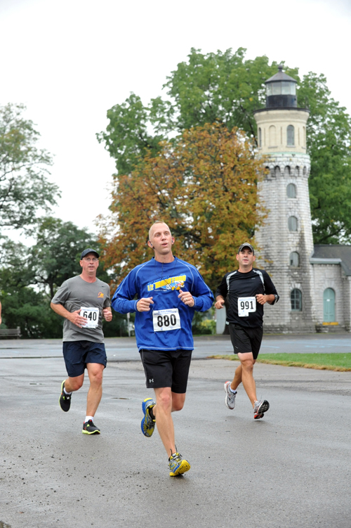 Chris McCaffrey, Jonathan Schultz, and Jeremy Traverse run past the historic lighthouse at Old Fort Niagara along the route of the Mighty Niagara Half Marathon.