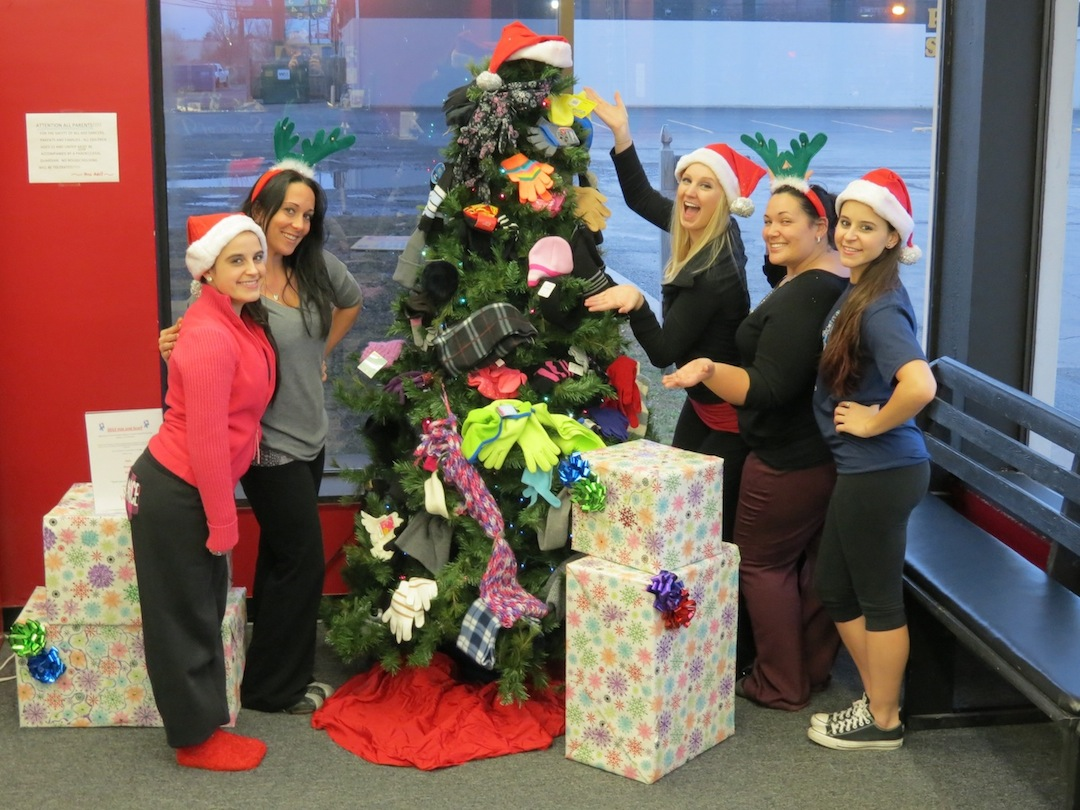 `Oh, the weather outside is frightful. But Adell's School of Dance's 'Christmas Xtravaganza' will be so delightful. And since we've no place to go, let's attend the show.` Adell Hoover (second from left) and her students pose by their studio Christmas tree, which is decorated with items that will be donated to the less fortunate.