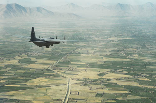 A C-130 Hercules from the New York Air National Guard flies over Afghan landscape on its way to delivering much-needed supplies to a forward operating base in Oruzgan province, Afghanistan on June 22.  (photo by Senior Airman Krista Rose)