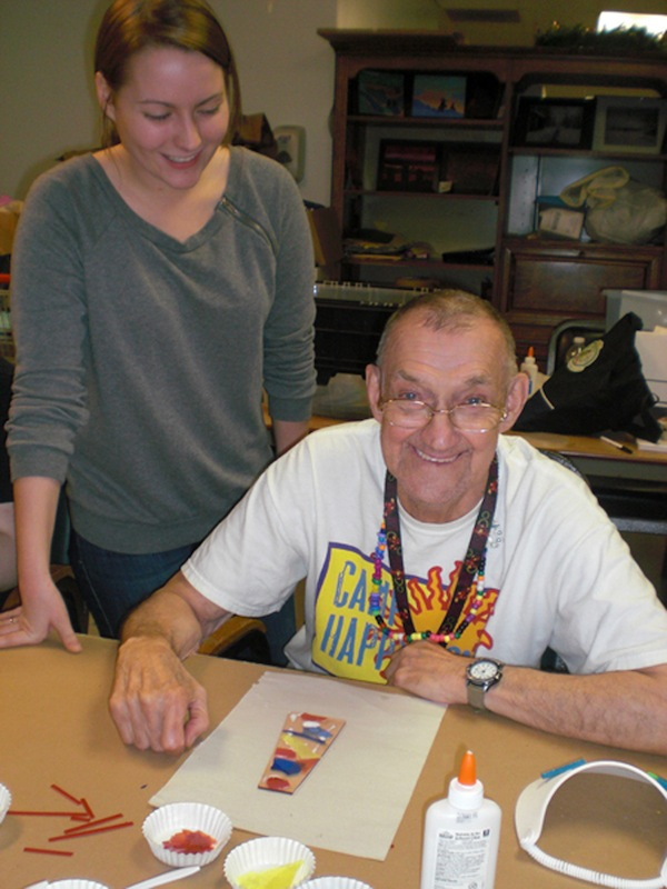 Artisans Unlimited of Opportunities Unlimited of Niagara participant Buddy Wall happily prepares a suncatcher, which will be sold at the 46th annual Lewiston Art Festival Aug. 11 and 12. Grigg-Lewis Foundation intern Lauren Ford provides guidance in working with glass.