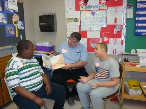 Orleans/Niagara BOCES students at the Lockport Learning Center spent several days making more than 100 valentines, which were passed on to the American Legion and to several senior residences. Shown are students Stefan Thornton (Niagara Falls) and Austin Marsh (Niagara-Wheatfield) reading a valentine book with teacher Mike Brauer.