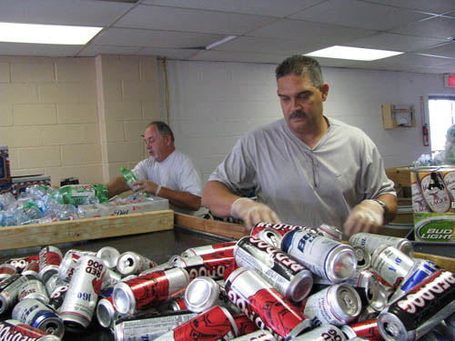 Bottle Junction owners Gary Herman, front, and Ray Pabon make short work of piles of bottles and cans at their new business at 3050 Niagara Falls Blvd., Wheatfield. (photo by Susan Mikula Campbell)