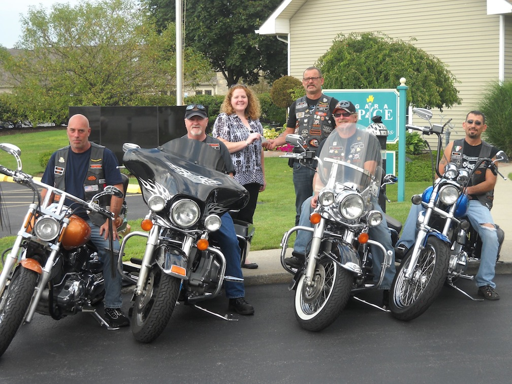 Pat Bondi, president of Eternal Brothers Motorcycle Club, presents a donation to Mandy Raff of the Niagara Hospice Alliance. Seated on their bikes, from left, are Bill Ferro, secretary; Joe Heeney, vice president; Duane Rickard, road captain; and Chris Bondi, treasurer.
