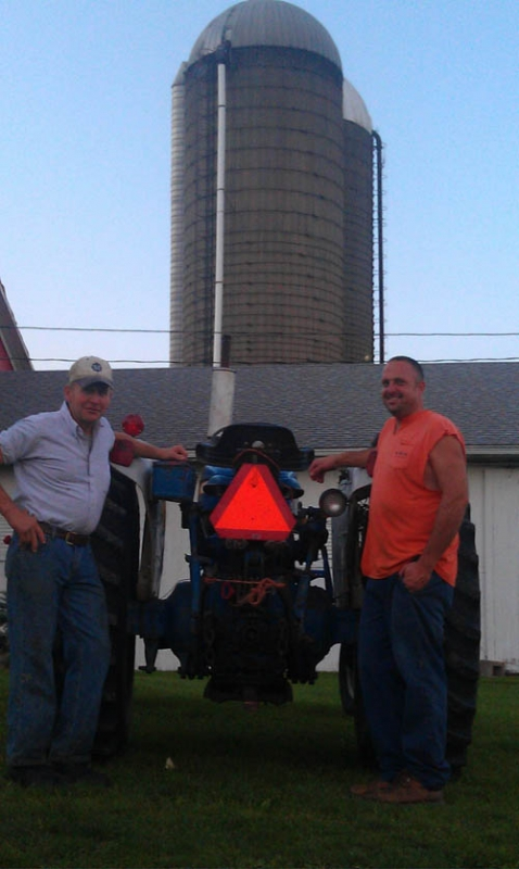Shown are Wheatfield farmers Nelson Haseley of Powerview Farms and Tom Hoover of Hoover's Dairy Farm standing next to a tractor marked with a slow moving vehicle sign at Haseley's Lockport Road farm. (photo by David Anastasi, member of Wheatfield's Agriculture Preservation Focus Group)