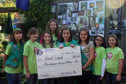 Presenting a check to Hawk Creek Wildlife Center are, from left, Girl Scouts Shavon Scive, Katie Mills, Rachel Redanz, Alexis Chase, Katie Miano, Hanna Cipollina, Gabriela Bonura and Samantha Ranney.