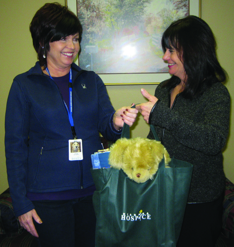 Niagara Hospice Director of Volunteer Services Alice Beck, at right, hands off a comfort tote to Hospice volunteer Ellen Gardner to deliver to a Hospice home care patient.