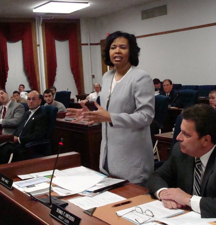 Niagara County Legislature Deputy Minority Leader Renae Kimble, D-Niagara Falls, debates a resolution from her desk on the floor of the County Legislature as Minority Leader Dennis F. Virtuoso, D-Niagara Falls (right) and Deputy Majority Leader Gerald K. Farnham, R-Pendleton (left) look on, in this undated photo.