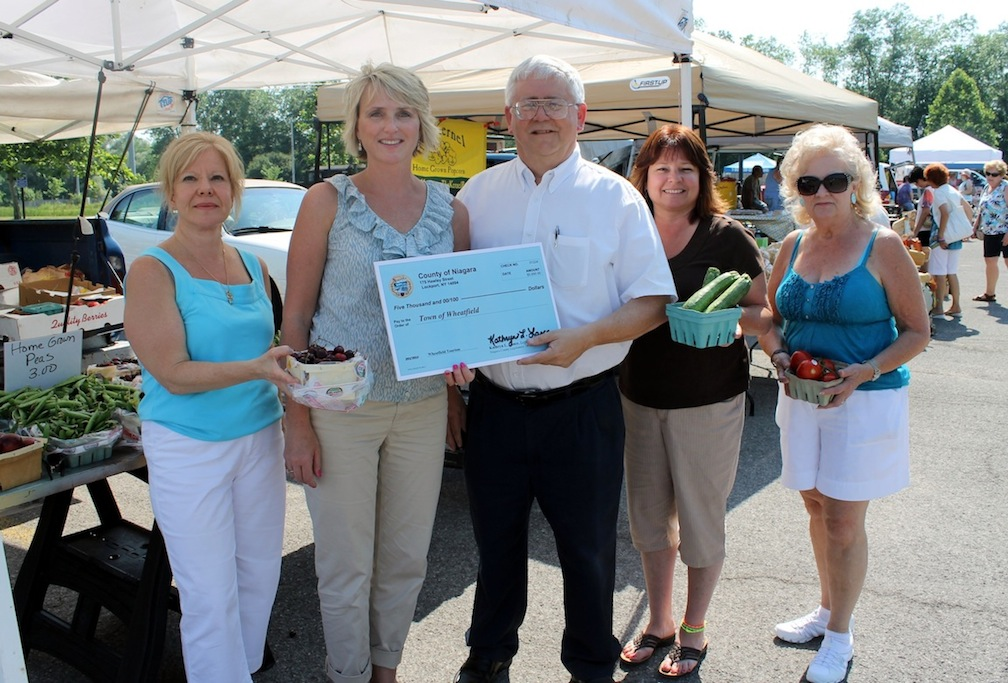 Wheatfield Town Clerk Kathy Harrington, left, and Wheatfield Town Supervisor Bob Cliffe accept a ceremonial check for $5,000 from Niagara County Legislator Kathryn Lance to fund a summer farmers market and a Fourth of July concert in the town. Also, Francine Boore and Diane Retzlaff display some of the produce available for sale at the weekly Wheatfield Farmers Market.