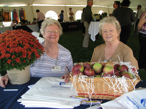 Hazel Baxter of Wheatfield and Carole Buchalski of Niagara Falls greeted visitors to the Grand Island event with smiles, a door prize drawing for fall flowers, and offers of fresh apples, granola bars and bottles of water. (photo by Susan Mikula Campbell)