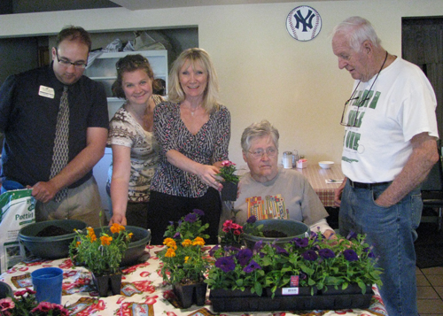 The activity at Memory Lane Café's May meeting was making pots of hanging plants to take home. From left, Kevin Maerten, Kashia Baldelli and Charlene Brosius from Peregrine's Landing Senior Community help Patricia Sturm as her husband, John, looks on.