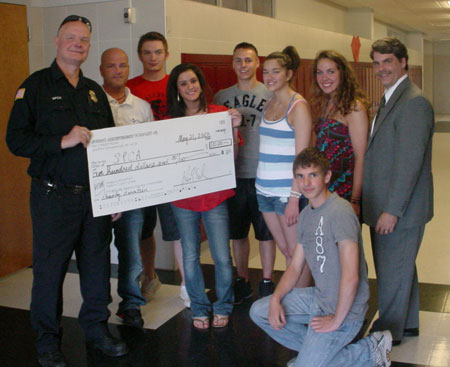 Presenting the check to the Niagara County SPCA's Robert Schildhauer (emergency rescue driver) are, from left, Kevin Schucker (Niagara-Wheatfield marketing teacher), Greg Janese (JA Company 3 - FalconHub Industries' vice president of public relations), Tamara Zeidan (vice president), Nick Hannam (vice president of finance), Alexxa Poliachik (vice president of human resources), Danielle Dworzanski, Jeremy Chapman (vice president of marketing) and Dan Caro (JA volunteer from the law office of Daniel Caro).